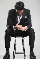 Elegant young man in tuxedo looking down while sitting on a stoo