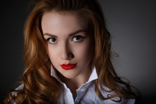 Beautiful young woman in a white man's shirt on dark background
