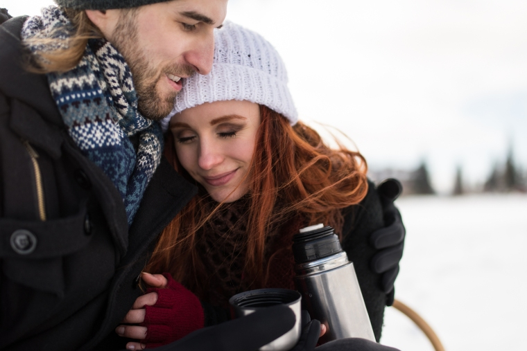 Redhead woman embracing her man on snowy winter day